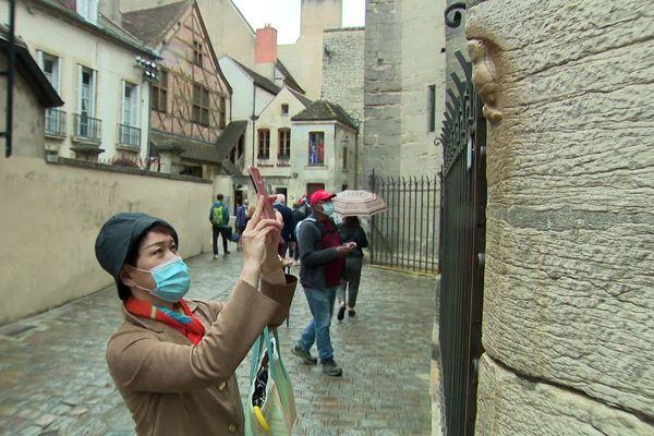 A Dijon, les touristes ne manquent jamais d'immortaliser la chouette sculptée sur Notre-Dame.