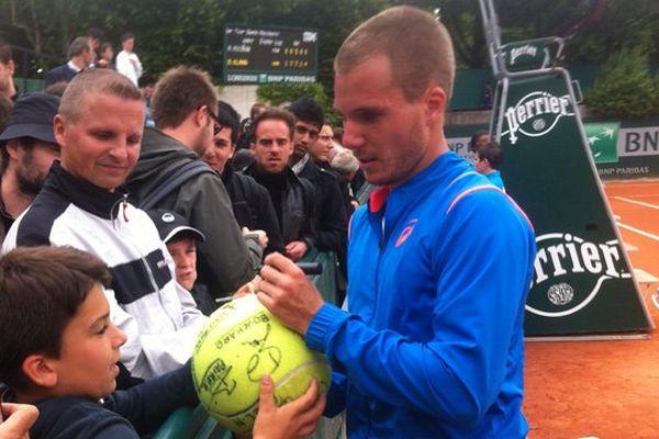 Le Granvillais Axel Michon signe un autographe après sa victoire en cinq sets au premier tour face à l'Américain Bradley Klahn, 73e joueur mondial