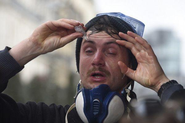 Un manifestant se lave les yeux avec une solution saline après les premiers gaz lacrymos