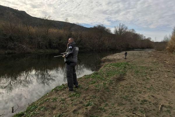 Un agent de l'office français de la biodiversité à l'affût avec son fusil hypodermique sur les berges de l'Agly - janvier 2021.