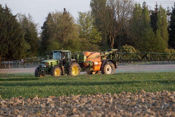 Un tracteur épandant des pesticides dans un champ. Photo d'illustration