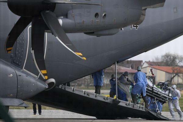 Les équipes médicales en train de transférer un malade à bord d'un avion médicalisé de l'armée allemande, sur le tarmac de l'aéroport de Strasbourg-Entzheim.