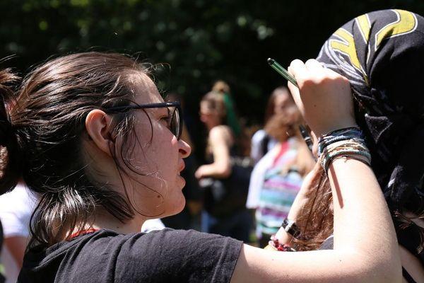 Maquillage, d'une larme de couleur verte, avant le départ de la manifestation pour le climat