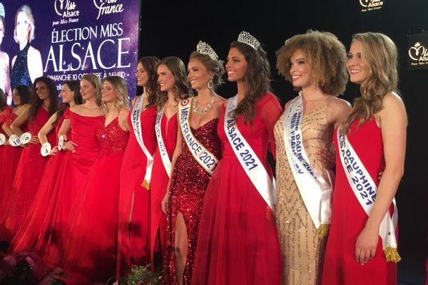 Miss Alsace et ses dauphines, accompagnées des autres candidates, toutes de rouge vêtues, sur la scène du CSI de Sélestat.