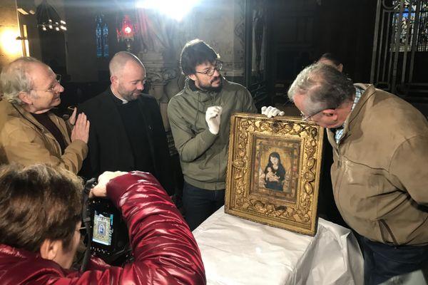 Jonathan Graindorge, restaurateur du patrimoine, explique aux responsables présents le protocole de restauration du tableau de Notre-Dame des Vertus, dont l'origine pourrait être antérieure à 1459.