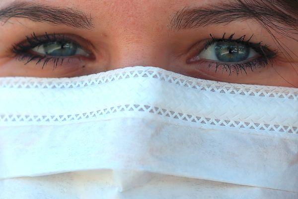 Une jeune femme porte un masque de protection durant la pandémie de Coronavirus Covid-19