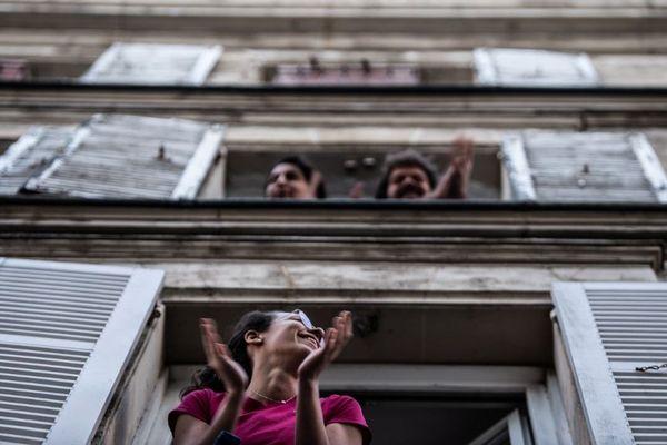 Des Parisiens applaudissent en hommage au personnel soignant à 20h. Photo prise le 14 avril 2020.