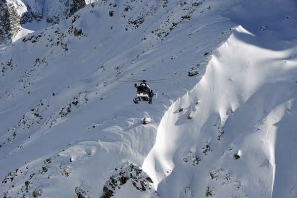 Un hélicoptère du Peloton de Gendarmerie de Haute Montagne (PGHM) survolant la Vallée blanche, dans le Massif du Mont Blanc. Image d'illustration.