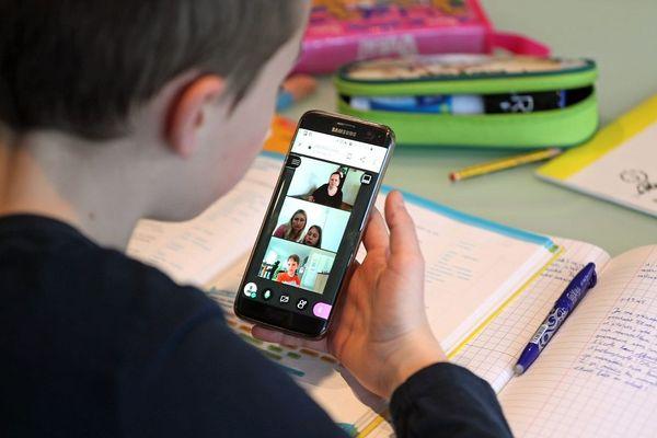 Un élève de CM2 en classe virtuelle sur son téléphone