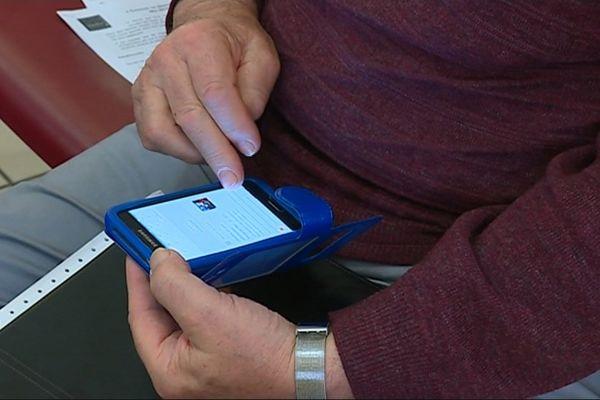 Un senior tient un smartphone dans sa main.