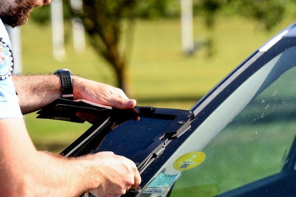 Un gendarme scanne une vignette Crit'air à l'aide de sa tablette.