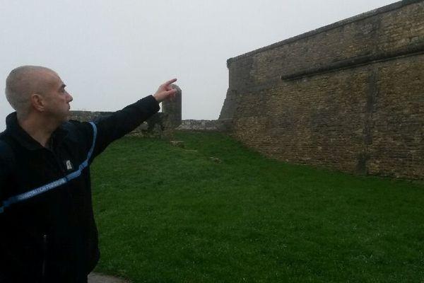 Un resposable syndical des gardiens de prison montre l'endroit par lequel se sont échappés les deux détenus en escaladant le mur de la citadelle.