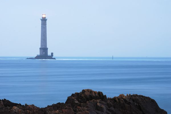 Dans le Cotentin, à l'horizon de la Hague, mer calme au crépuscule vers le phare de Goury.