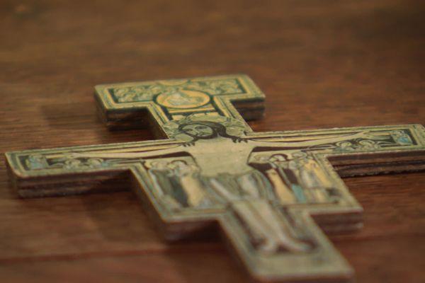 Une croix disposée sur la table, au cœur de la salle où le prêtre reçoit son public.