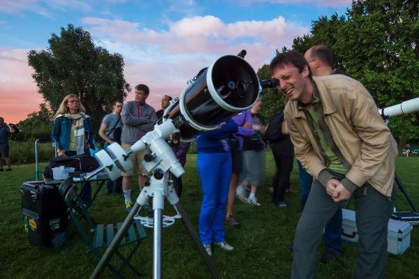 À Villeneuve-d'Ascq, un homme observe le ciel au travers d'un télescope, accompagné d'astronomes du club astronomique de la région lilloise, lors des Nuits des étoiles de 2014.