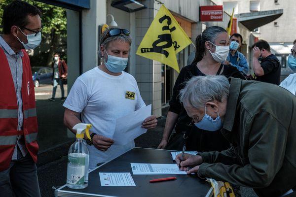 Devant le bureau de poste, les représentants syndicats font signer une pétition aux habitants de la Benauge, ce lundi 7 juin à Bordeaux.