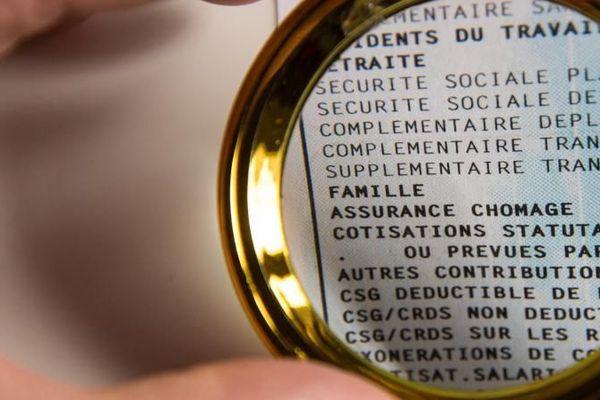 Un bulletin de paie vu à travers une loupe à Paris, le 5 février 2019.