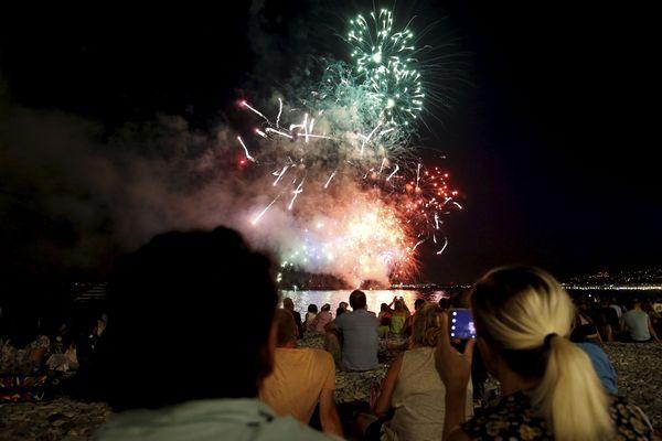 Des personnes profitent du feu d'artifice sur la plage, le 13 juillet 2019, à Nice.