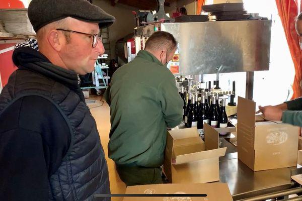 """David Béroujon (à gauche) est un viticulteur comblé : son Beaujolais-Villages 2020, élu par le jury du """"Meilleur Gamay du monde"""", est désormais mis en bouteille. Une opération qui a nécessité beaucoup de concentration : pas question de gâcher un seul des 13 000 flacons mis en carton ce jour."""
