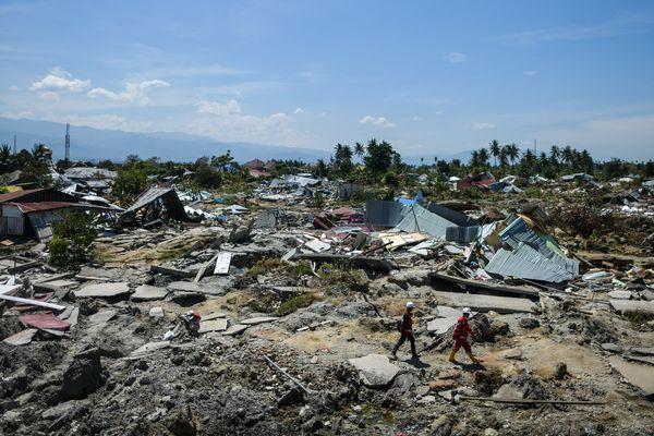 Des sauveteurs passent à travers les débris à Palu (Indonésie), le 5 octobre 2018.