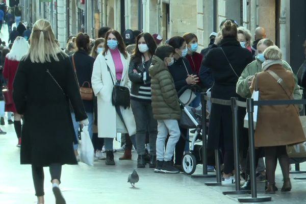 Les acheteurs patientent masqués avant de pouvoir pénétrer dans les boutiques, rue Sainte-Catherine à Bordeaux.