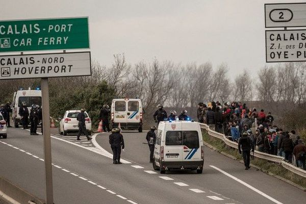 "Policiers et CRS tentent d'éloigner les migrants de la ""jungle"", aux abords de la rocade portuaire, le 25 novembre 2015."