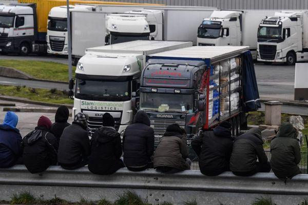 (Archive). Des migrants assis sur une rambarde, le 3 février 2018 dans la zone portuaire de Calais.