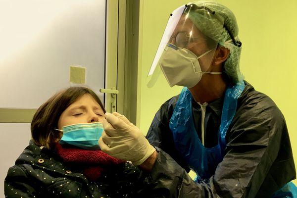 Une infirmière pratique un prélèvement avec Rose (6 ans) pour un test antigénique dans un centre dédié à Rezé en Loire-Atlantique