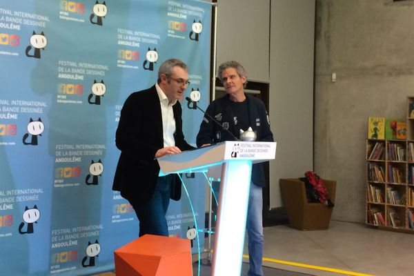 Le Grand Prix est remis par Cosey (à droite) à Laurent Lerner, de Delirium, l'éditeur de Richard Corben (au pupitre).