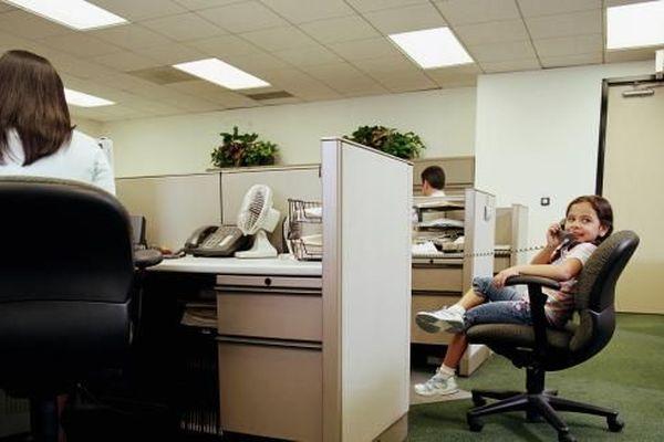 Une petite fille dans un bureau patiente en passant un coup de fil.