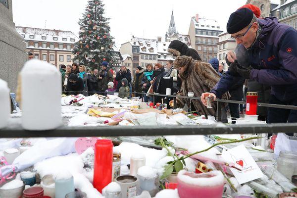 Des personnes déposent des bougies au pied du mausolée de Kléber en marge de l'hommage rendu dans la capitale alsacienne aux victimes de l'attentat de Strasbourg, le 16 décembre 2018.