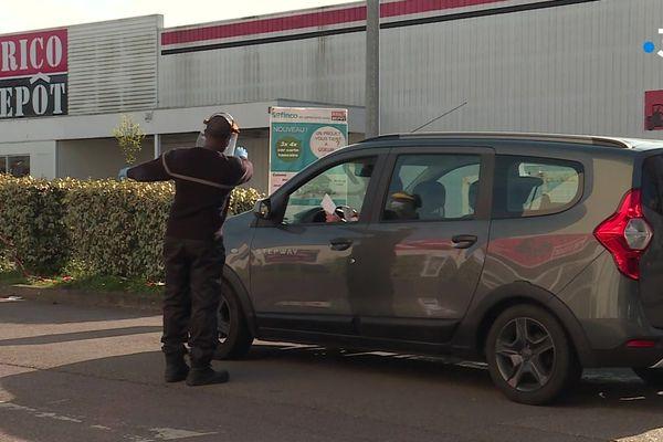 Rouen le 7 avril 2020 : un agent de sécurité casqué, ganté, masqué et avec une visière, accueille les voitures des clients venant chercher leur commande dans une enseigne de bricolage