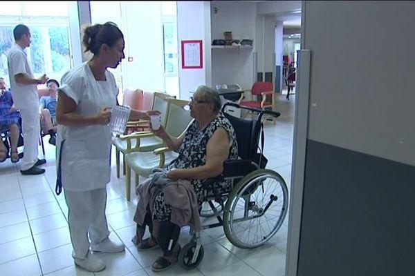 Une soignante donne à boire à une résidente dans une maison de retraite de la Côte d'Azur.