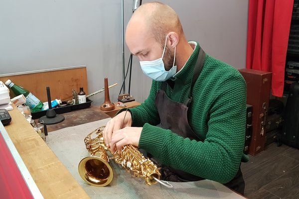 Sylvain Lecocq, facteur d'instruments à vents, rectifie le bouchage sur les cheminées d'un saxophone d'études