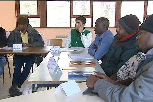 Des migrants suivent un cours de mathématiques au centre d'accueil de Saint-Beauzire (43).
