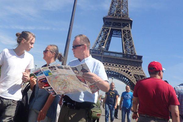 Des touristes au pied de la tour Eiffel, à Paris.