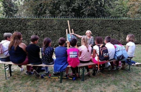 Martine, bénévole de Lire et faire lire, conte une histoire à des enfants de primaire, dans les jardins du palais du gouvernement à Nancy (54), à l'occasion du Livre sur la place 2019.