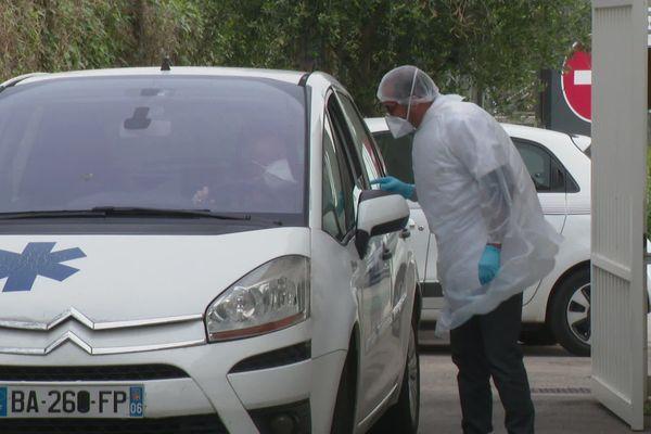 Un biologiste s'apprête à tester un soignant dans un drive d'un laboratoire d'Antibes.
