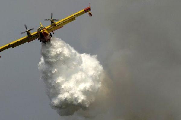 Un avion bombardier lâche de l'eau sur les flammes.