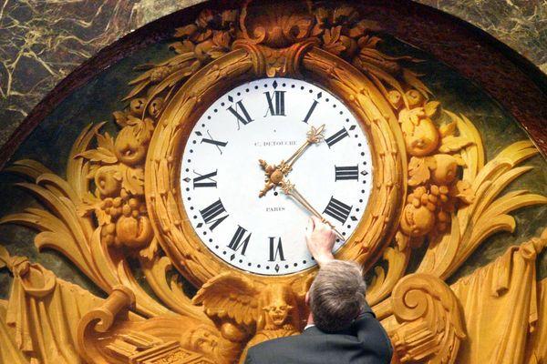 Un homme change l'heure sur l'une des horloges du château de Versailles.