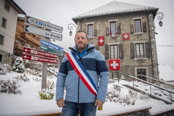 Nicolas Rubin, maire (DVD) de Châtel, en Haute-Savoie, pose devant la mairie décorée avec des drapeaux suisses pour protester contre la fermeture des remontées mécaniques.