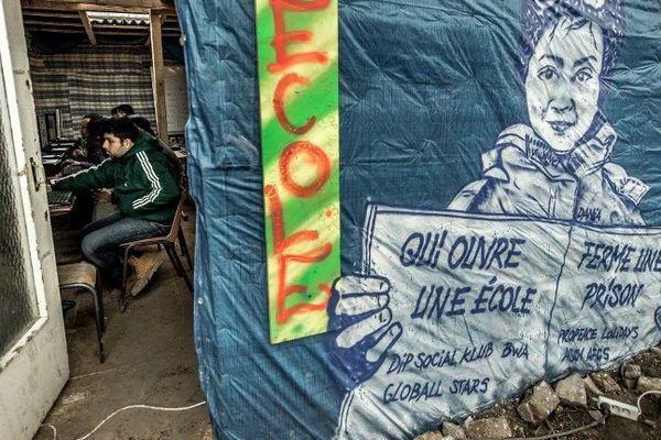 """Des migrants utilisent des ordinateurs dans l'école laïque de la """"Jungle"""" de Calais, qui pourrait être détruite dans les prochains jours."""