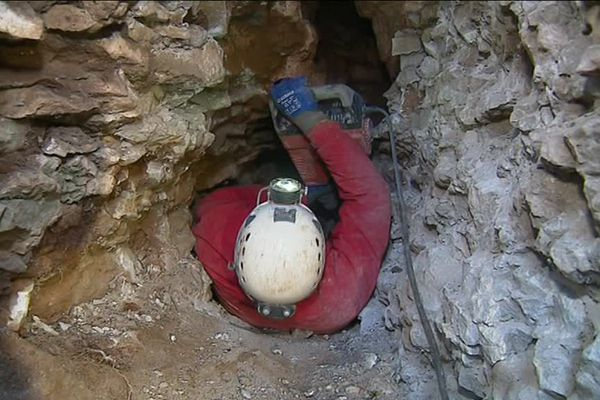 Un spéléologue agrandit le passage permettant d'accéder à des chiens coincés dans une cavité à Grésigny-Sainte-Reine en Côte-d'Or en 2018.