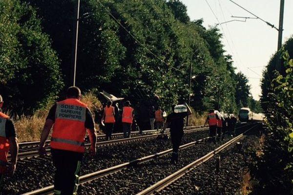Des personnels de la SNCF apportent de l'eau aux passagers d'un TGV et inspectent les voies, suite à la collision entre une rame et les débris d'un tracteur sur la voie.