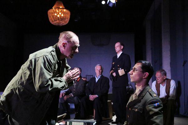Les comédiens en répétition : un enquêteur américain pose une question à un prisonnier.
