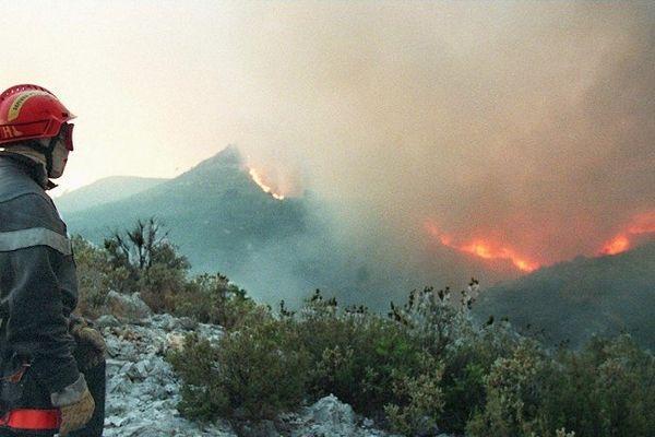 Un sapeur pompier regarde le feu qui se propage dans le massif du Garlaban, dans la nuit du 26 au 27 juillet, 1997 - photo Georges Gobet - Afp