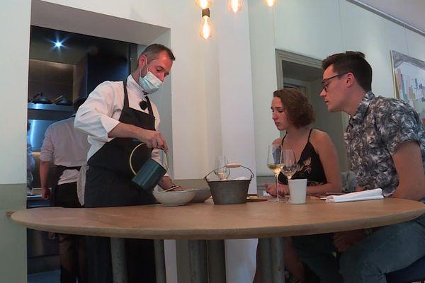 Le chef étoilé du Jardin des plumes (Giverny) David Gallienne présente aux clients les plats qu'ils vont déguster. Au menu : le champignon de Paris et son bouillon d'inspiration thaï.