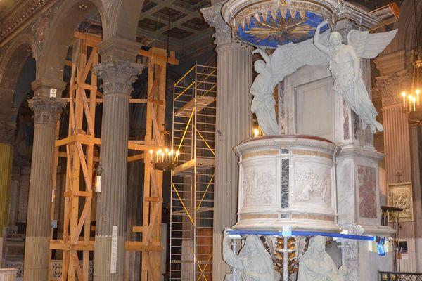 En second plan, un échafaudage en bois retient l'une des parties de l'église.