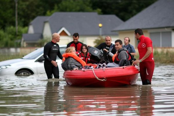 Les pompiers et les secouristes évacuent les habitants du village de Nay, complètement inondé, le 19 juin.