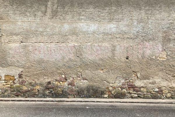 Les inscriptions sur le mur du cimetière et sur la grange (ici) ont été rapidement effacées. On voit la différence de teinte sur la pierre.